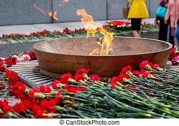 Eternal fire and flowers in memory of victims in the world war on victory day on 9 may.Burning eternal fire at the memorial to fallen soldiers
