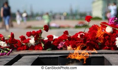 Eternal fire burns in afternoon at Monument to victims of...