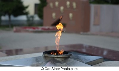 "Eternal Flame - symbol of victory in World War II. Burning eternal flame and star at mass tomb of soldiers. ""Eternal Flame"" at the memorial to fallen defenders the motherland. Eternal fire burns against a granite roadway. Fire"