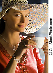 A beautiful young brunette woman drinking a cup of tea or coffee lit buy beautifully golden and soft natural light