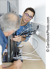 ethernet cable being plugged into a wall socket