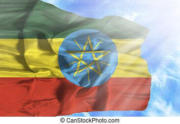 Ethiopia waving flag against blue sky with sunrays