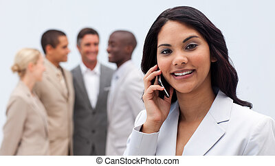 Ethnic businesswoman on phone with her team in the background