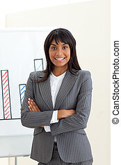 Ethnic businesswoman with folded arms in front of a board...