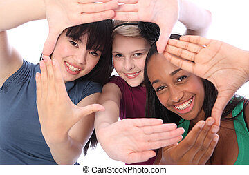 Fun hand sign by three multi cultural teenage school student friends made up of mixed race african american, oriental Japanese and caucasian all happy holding hands out to camera.
