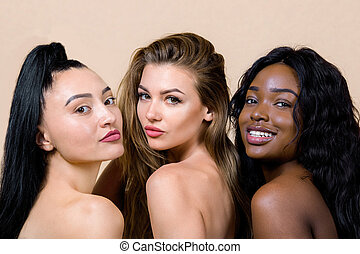 Ethnic diversity. Beauty close up portrait of three charming young multiracial women, Asian, Caucasian and African, with nude makeup and perfect skin, standing together against beige background
