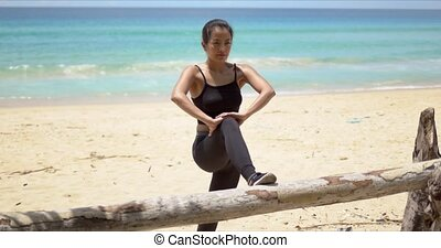 Ethnic female warming up on beach - Strong ethnic woman in ...
