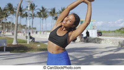 Ethnic sportive woman training in sunlight
