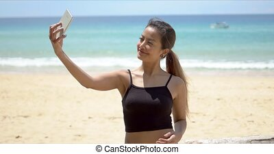 Ethnic sportswoman taking selfie on beach - Confident ethnic...