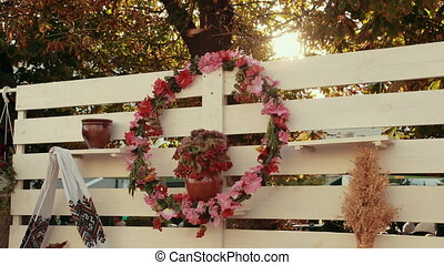 Ethnic Ukrainian folk photozone in traditional authentic style outdoors. Floral wreath, decorative embroidered towel, bunch of wheat, guelder rose look beautiful in sunlight.