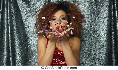 Ethnic woman blowing at confetti