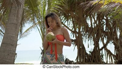 Ethnic woman enjoying coconut drink - Slim ethnic female ...
