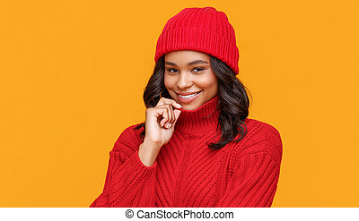 Positive ethnic female in trendy red sweater and hat smiling and looking at camera against yellow background