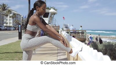 Ethnic woman leaning on fence while working out - Side view...