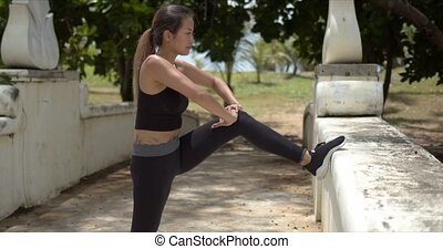 Ethnic woman stretching legs on bridge - Side view of fit ...