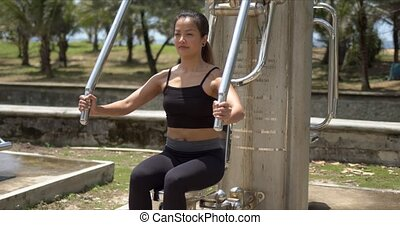 Ethnic woman using chest press machine on resort - Slim ...