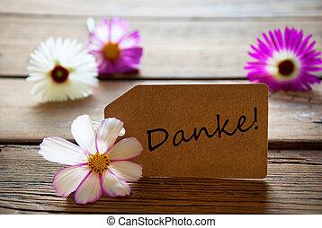 etiqueta, con, texto alemán, danke, con, cosmea, flores