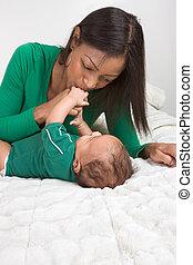 etnisk, mor spela, med, henne, baby pojke, son, blomsterbädd