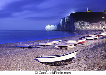 Etretat village, bay beach and boats on foggy night. Normandy, France.
