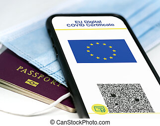 EU Digital COVID Certificate with the QR code on the screen of a mobile phone over a surgical mask and a passport