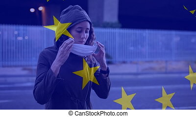 Animation of EU flag waving over Caucasian woman holding a face mask. Covid-19 coronavirus national health safety concept digital composite