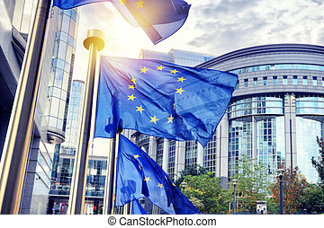 EU flags waving in front of European Parliament building in Brussels