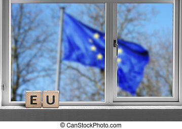 EU sign in a window with the European union flag
