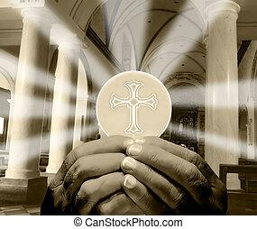 Eucharist - hands holding Eucharist in a church interior