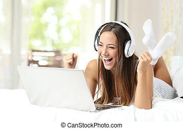 Euphoric winner watching media in a laptop