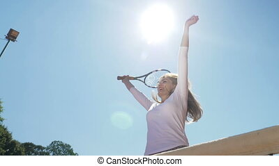 Euphoric woman jumping happily with tennis racket in hand...