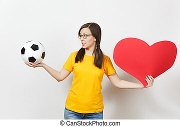 európai, fiatal, bús, felborít, nő, póni frakk, foci rajongó, vagy, játékos, alatt, szemüveg, sárga, egyenruha, befolyás, klasszikus, labda, nagy, piros szív, elszigetelt, white, háttér., sport, labdarúgás, egészséges életmód, concept.