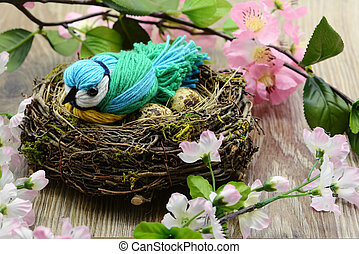 Eurasian blue tit (Cyanistes caeruleus) made of wool parts sitting in a nest