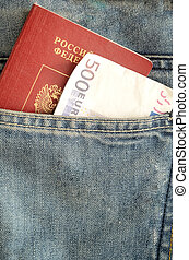 Euro banknote and a Russian passport in the pocket of blue jeans.