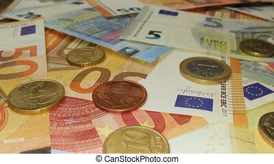 Pile of Different Euro banknotes and coins, macro shot, sliding camera motion