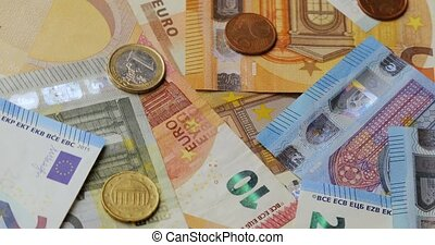 Pile of Different Euro banknotes and coins, macro shot, spinning in 60fps