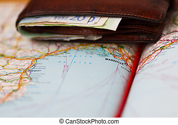 Euro banknotes inside wallet on a geographical map of Marseille