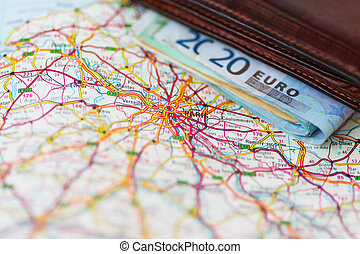 Euro banknotes inside wallet on a geographical map of Paris