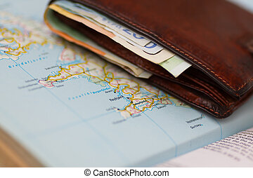 Euro banknotes inside wallet on a geographical map of Reykjavik