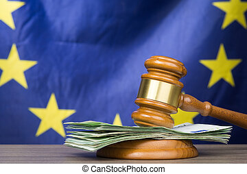 Euro banknotes with a wooden court gavel against european union flag as a concept of corruption in the judicial system