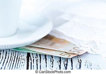 euro bill with coins and cup of coffee on wooden table. Payment, tip.