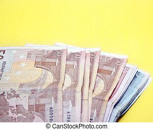 euro bills on yellow background
