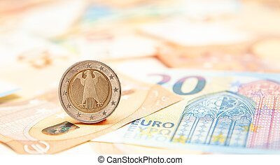 Euro coin rolls against a background of banknotes.
