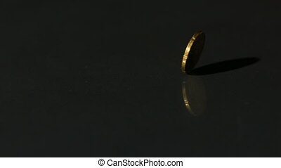 Euro coin spinning on black surfac