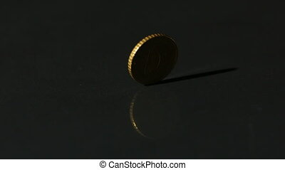 Euro coin spinning on black surface in slow motion