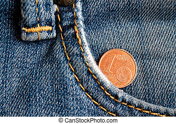 Euro coin with a denomination of 1 euro cent in the pocket of old worn blue denim jeans