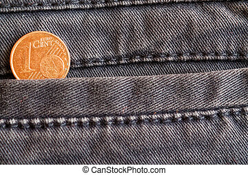 Euro coin with a denomination of 1 euro cent in the pocket of worn blue denim jeans