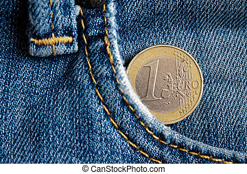 Euro coin with a denomination of 1 euro in the pocket of blue denim jeans