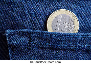 Euro coin with a denomination of 1 euro in the pocket of old worn blue denim jeans