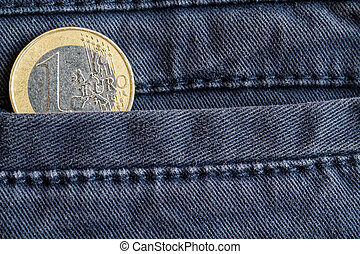 Euro coin with a denomination of 1 euro in the pocket of worn blue denim jeans
