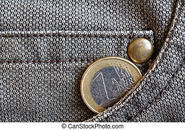 Euro coin with a denomination of 1 euro in the pocket of worn brown denim jeans